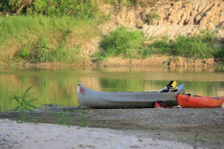 Staff photo by Minza KhanHarris County canoes sit near the creek while memebers take a break. Photo: Minza Khan