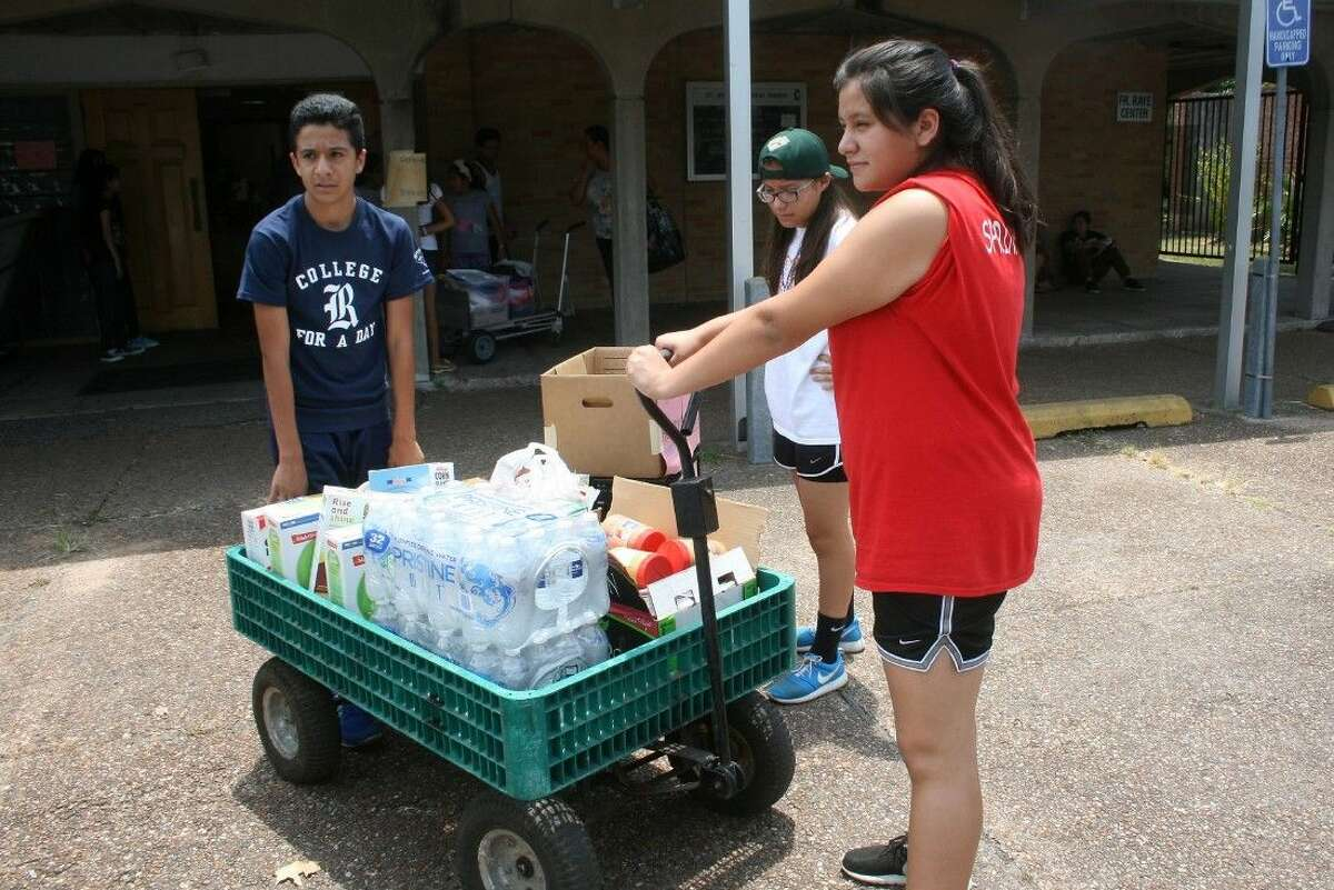 L to R: Jonathan Rodriguez, 13, Jazmin Zuniga, 13, and Melane Esparza, 15, parishioners of St. Jerome's Catholic Church deliver a cart of supplies to a victim's car.