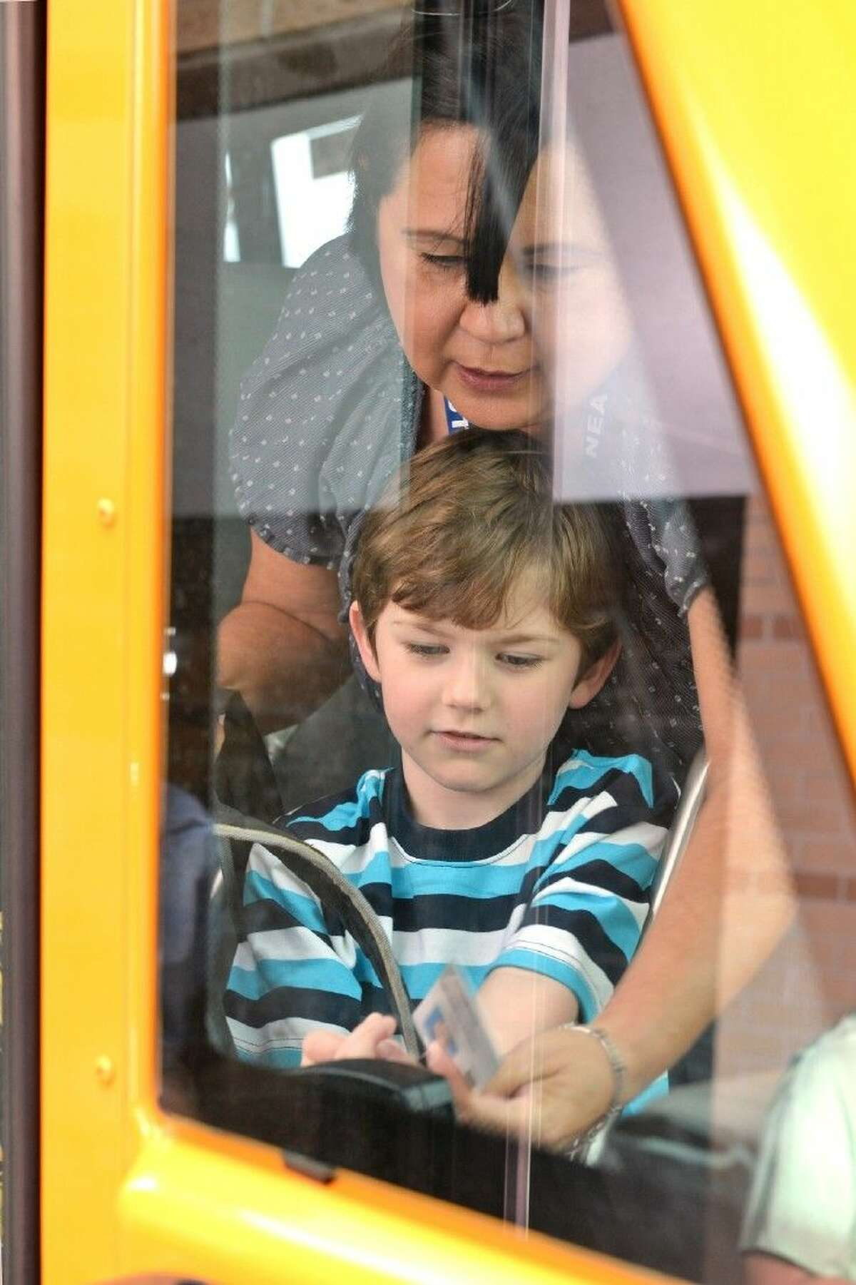 Bus driver Norma Elizondo from the Falcon Transportation Center assists Willbern Elementary School second-grade student Sean Dionne as he scans his ID card while boarding a bus.