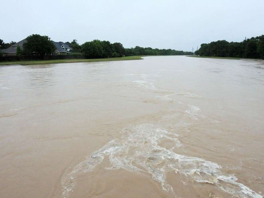 Buffalo Bayou was near the top of its bank near Mason Road in the Cinco Ranch area early Monday. The bayou was one of at least 13 to break their banks as a result of widespread downpours Sunday night and Monday morning. Photo: Craig Moseley