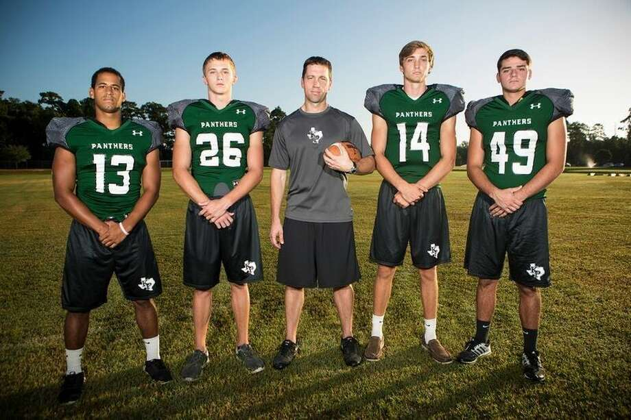 Panthers linebacker Dominic Kelley (13), safety Austin Harris (26), head coach Clayton Maple, quarterback Zach Purcell (14) and wide receiver Garrett Sweeney (49) pose for a portrait Aug. 5, 2015, at Kingwood Park High School.