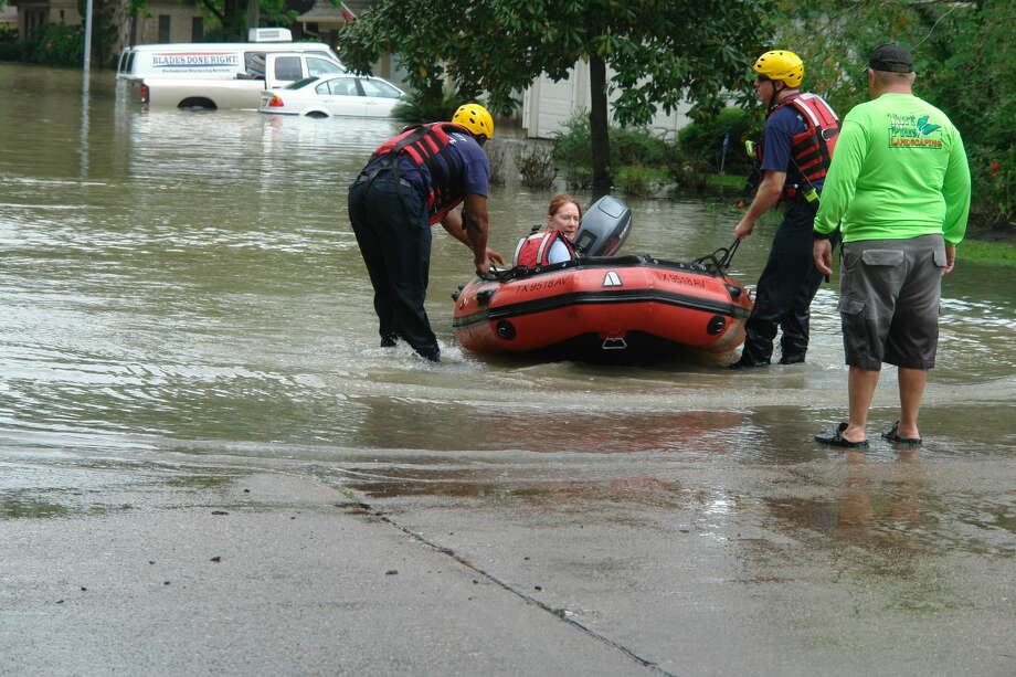 Firefighters help a stranded resident get out of her flooded neighborhood in northwest Harris County. Photo: Roy N. Kent