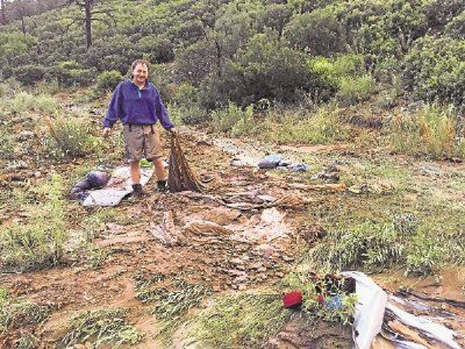 Associate Advisor J. Brigman with remains of tent that bore the brunt of the flood.