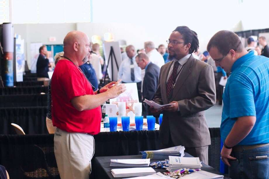 Greg Penton speaks with Pierre Mao at Military to Maritime Career Information Day at the Bayport Cruise Terminal Tuesday. Photo: KIRK SIDES