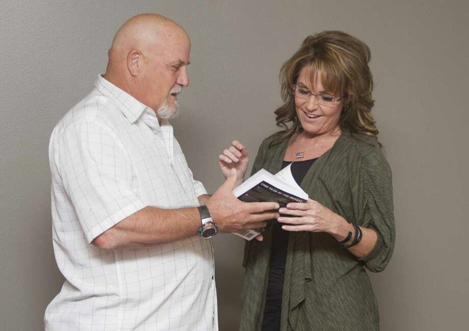 """Staff photo by Jason FochtmanErnie Carr presents Sarah Palin with the book """"Year of the Monkey"""" before speaking at a gala fundraiser event benefiting Mighty Oaks Warrior Foundation at WoodsEdge Community Church Friday. Photo: Jason Fochtman"""