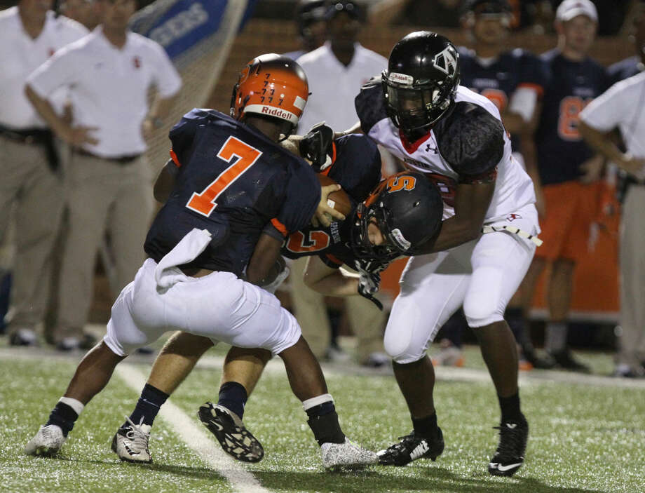 Austin's Lucas Boney sacks Seven Lakes' Tristan Hibbeler during a non-district game Sept. 5 at Rhodes Stadium in Katy. The Bulldogs shut out Hastings 17-0 on Oct. 17. Photo: Staff Photo By Alan Warren