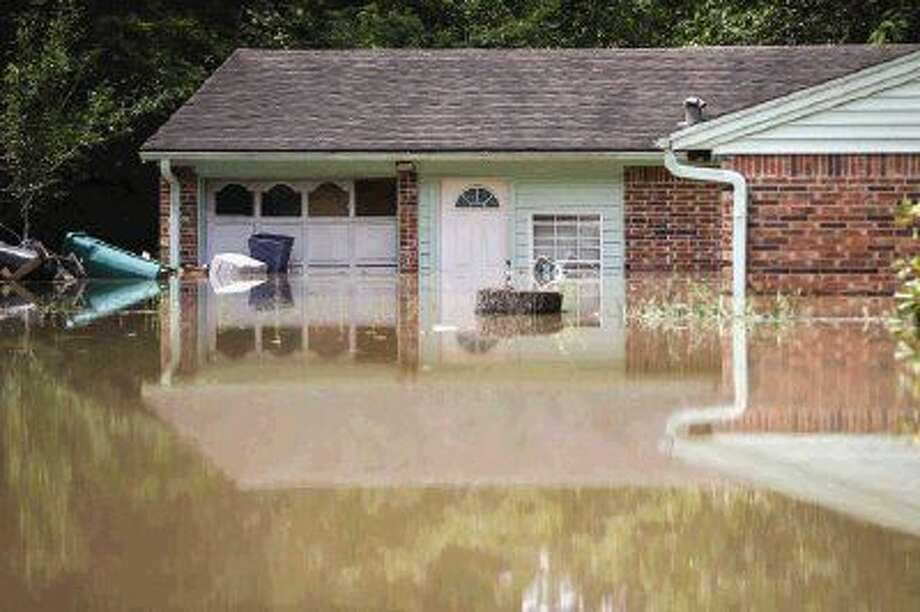 A home is pictured half submerged in the Timber Ridge / Timber Lakes subdivision on Tuesday.
