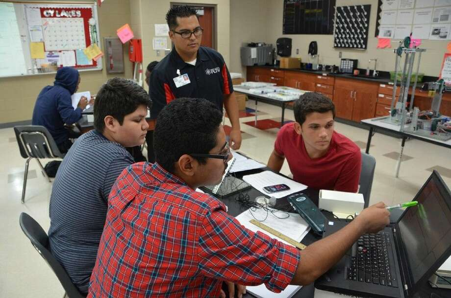 Submitted photoCypress Lakes High School Project Lead The Way (PLTW) engineering teacher Giovanni Neri reviews an in-class project from sophomore students Jesus Castillo Jr., Diego Ferman and Jacob Sanders. Photo: Submitted Photo
