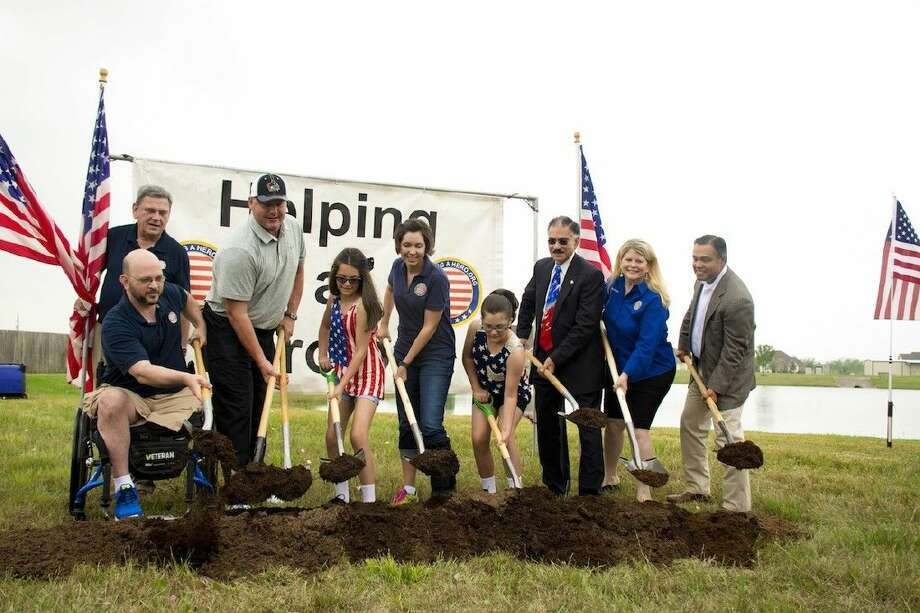 Sante Fe residents SGT (Ret) Daniel Cowart, USA and his family - wife, Sarah, daughters Avalon and Alyssa - pose for a picture at Helping A Hero groundbreaking ceremony where their new home will soon be built.