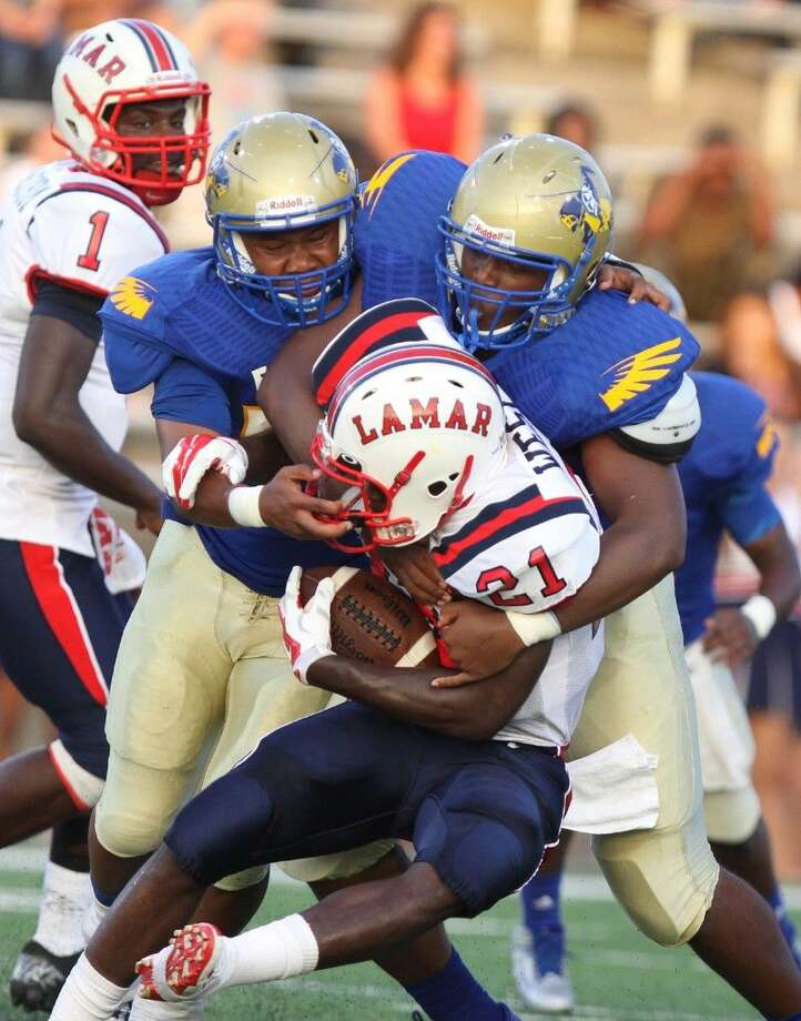 Photo by Alan Warren/Houston Community NewspapersElkins' Brandon Jones and Malik Williams stop Lamar's Ronnie Wesley on Sept. 6 at Mercer Stadium. Photo: Alan Warren