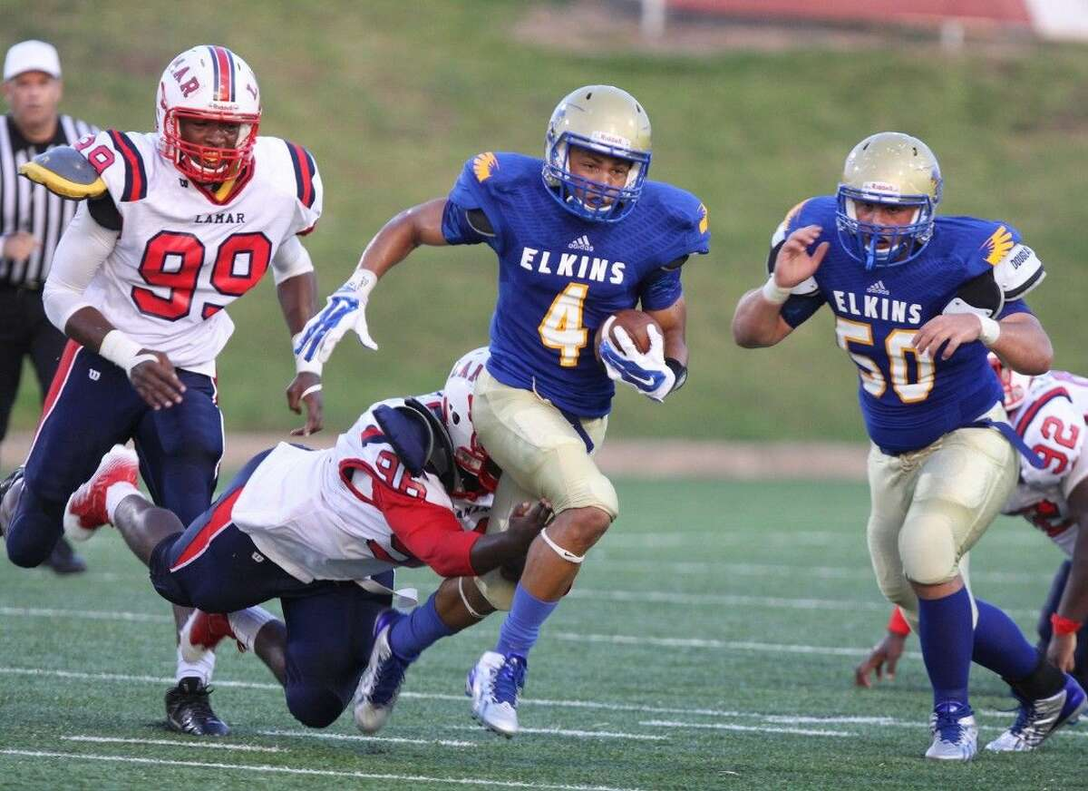 Photo by Alan Warren/Houston Community NewspapersElkins' Andre Mathews runs against Lamar's Chastin Lee during their Sept. 6 non-district game at Mercer Stadium in Sugar Land. The Knights won 21-13.