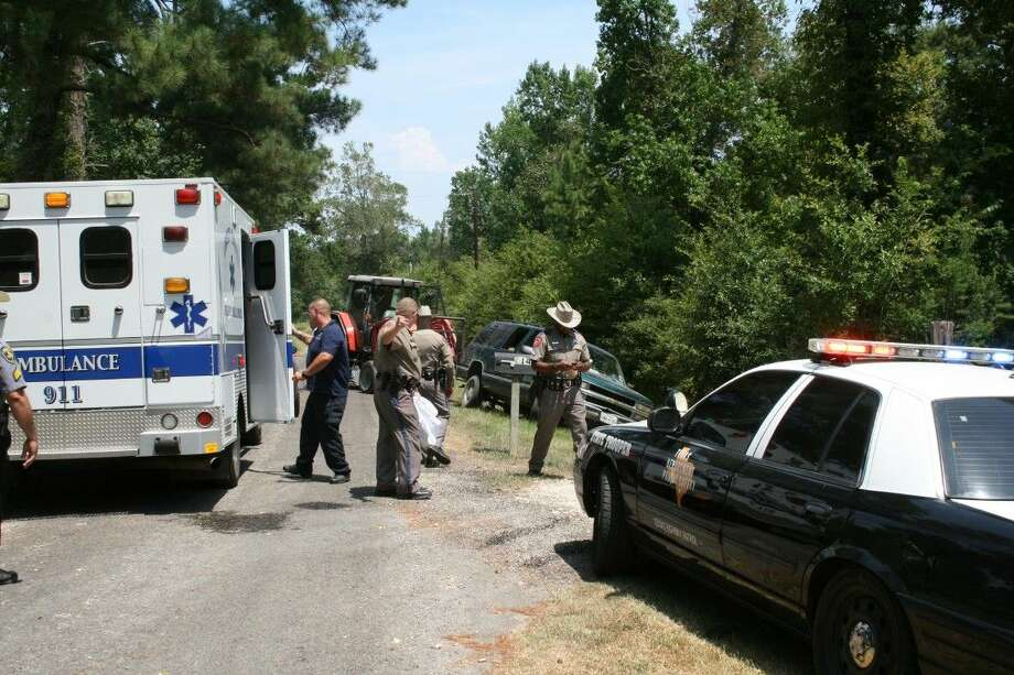 Texas Department of Public Safety troopers from Liberty County, under the direction of Sgt. Rob Willoughby, investigate an accident on CR 2255 in the Davis Hill area on Tuesday where a young girl was thrown from a trailer and pinned underneath it. Photo: Vanesa Brashier
