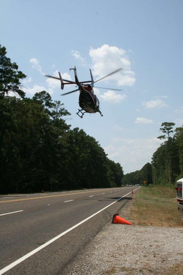 A LifeFlight helicopter prepares to land on SH 105 near Davis Hill where 14-year-old Jessica Bounds was seriously injured Tuesday, Aug. 11, when she fell from a trailer being towed behind a vehicle. She was airlifted to Memorial Hermann Hospital in Houston. Just an hour or so later, her father died from health-related issues. Photo: Vanesa Brashier