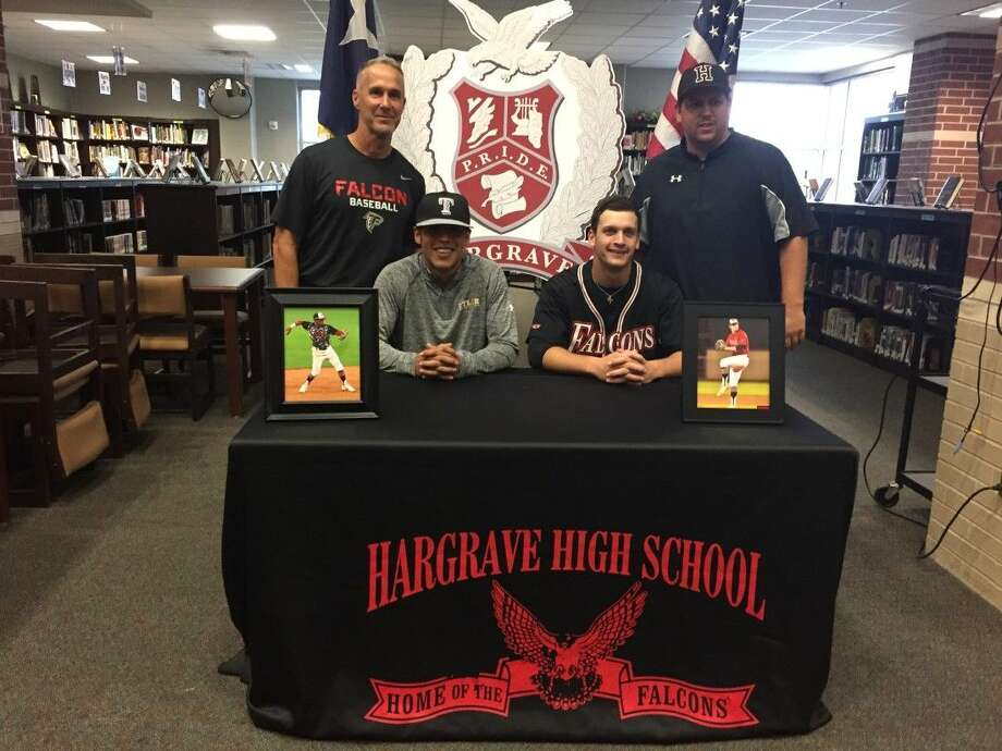 Huffman coaches Tom DeBerry (left) and Troy Sample (right) join Cody Gaitan (left front) and Justin Waltmon (right front) after the duo signed National Letters of Intent to play college baseball on Wednesday, April 20, 2016 at Huffman High School.