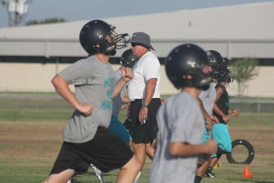 Memorial head football coach Chris Quillian is framed by his players doing some practice-opening sprints Monday. Photo: Robert Avery