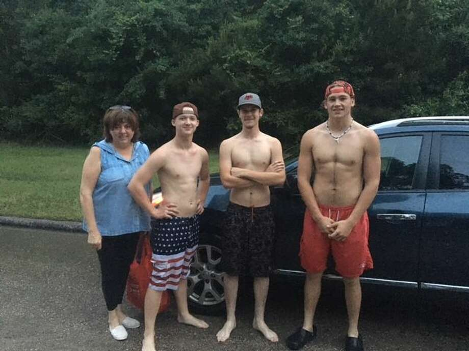 Carol Larson, of Enchanted Oaks, stands beside Harry Broadway, Cheyne Sims and Josh Merrilat moments after they rescued her 2013 Nissan Rogue from floodwaters caused by the torrential downpour Sunday night and Monday morning. Photo: Dylan Bailes