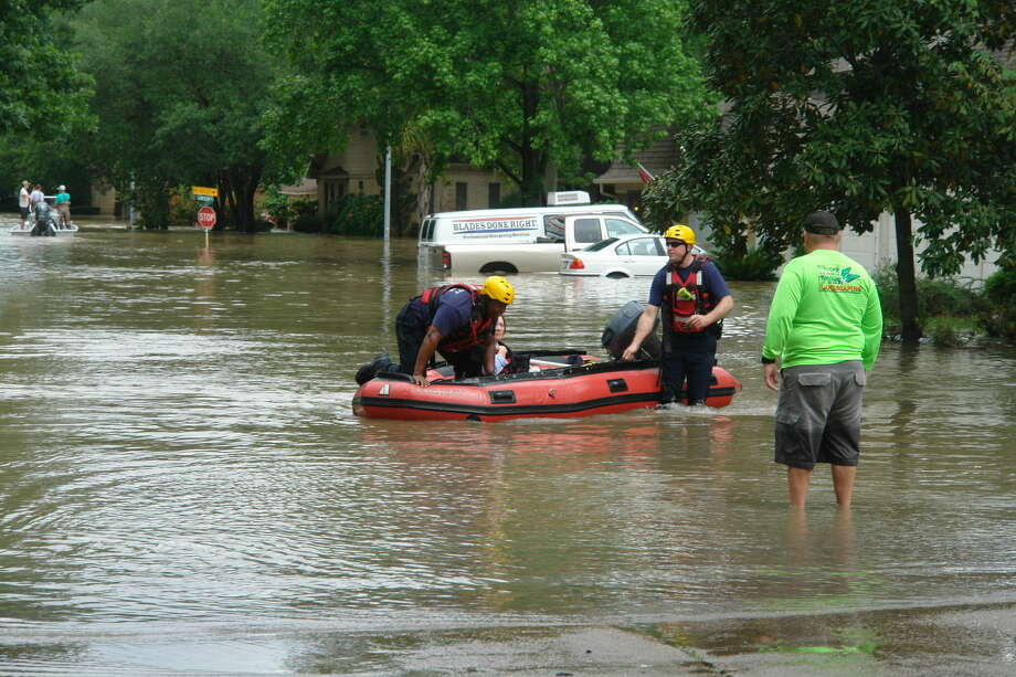 A resident is brought to safety on Tuesday, April 19, in the Norchester neighborhood of northwest Harris County. Photo: Roy N. Kent