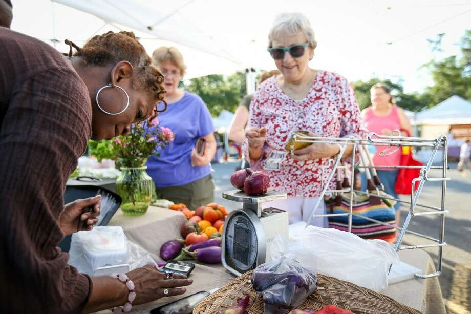 Lucinda Deason, of Holistic Organic Foods, rings up an order for a customer Saturday at the Grogan's Mill Farmer's Market. Photo: Michael Minasi