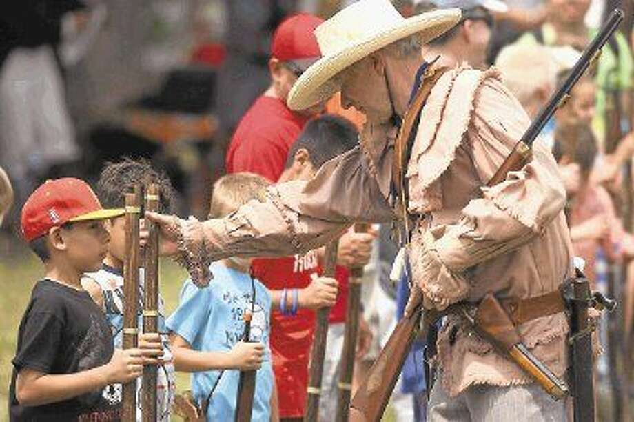 A reenactor show proper musket useage to kids as they are invited to march with them at the San Jacinto Day Festival. Photo: Kar B Hlava