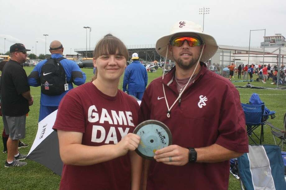 Brittni Mohle and coach Zack Whitaker savor the newly-earned trip to the Region III meet in the discus event Thursday afternoon. Mohle captured third place to keep her season alive. She later qualified for regionals in the shot put. Photo: Robert Avery