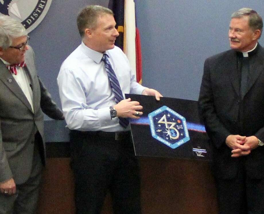 Astronaut Terry Virts (center) presented members of the Friendswood ISD Board of Trustees with a photo montage created using pictures he took from the International Space Station at a meeting held Monday (April 11). Pictured left to right: Board Vice President Matt Robinson, Virts, Trustee Ralph Hobratschk Photo: Kristi Nix