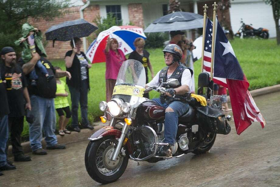 "A member of The Patriot Guard rides past friends, family and the community during a ""rolling tribute"" welcoming U.S. Marine Corps Sgt. Robert Lavachery home after eight years of military service Sep. 7, 2014, in Atascocita. Photo: ANDREW BUCKLEY"