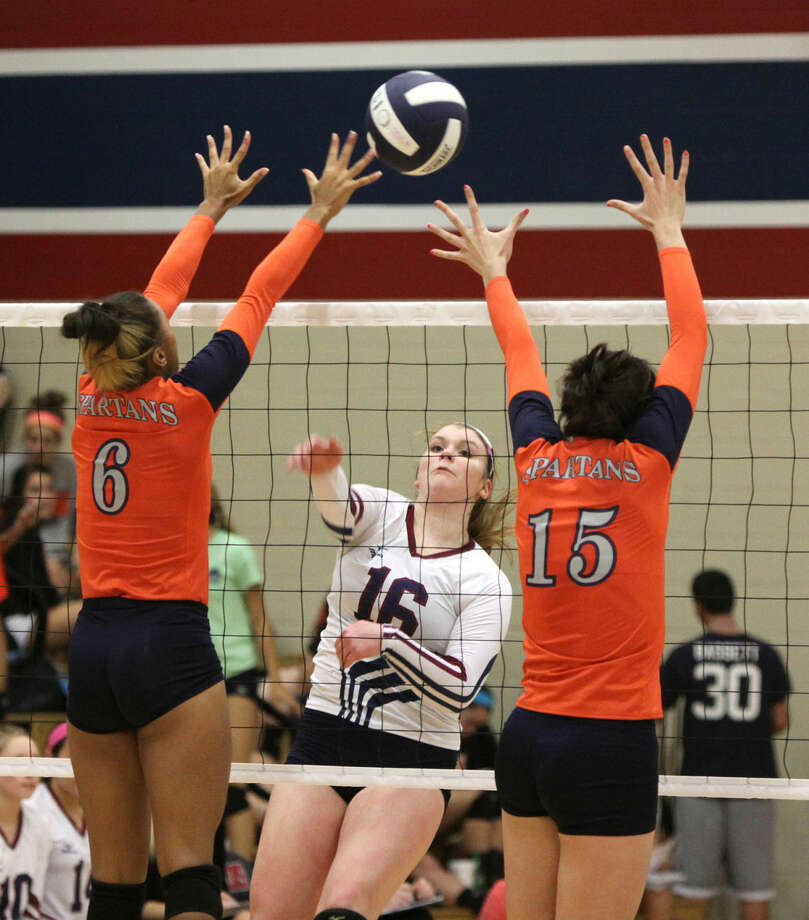 Tompkins' Katelyn Finch splits Seven Lakes' Michaela Daniels and Maggie O'Connell during a District 19-6A volleyball game Oct. 7 at Tompkins High School in Katy. To view or purchase this photo and others like it, go to HCNPics.com. Photo: Staff Photo By Alan Warren