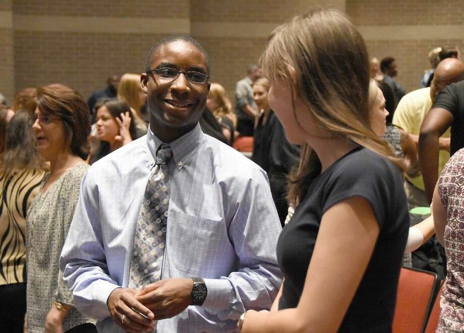 Rashid Lane, first-year Cypress Lakes High School art instructor, speaks with another new hire during the New Staff Orientation at Cypress Lakes in August 2015. CFISD hired more than 800 new staff for the 2015-2016 school year.