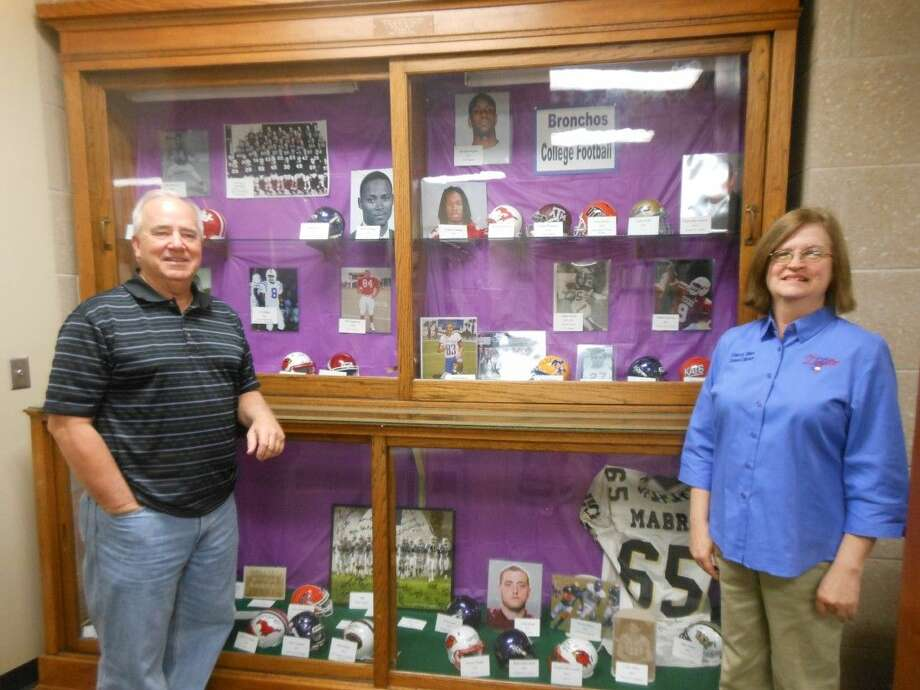 Larry Wadzeck and Sherri Sikes stand before the new display at Jones Public Library in Dayton. Wadzeck compiled artifacts to create a display to honor some of the collegiate successes of Dayton Bronco student-athletes. Sikes is the director of Jones Public Library. Photo: Submitted