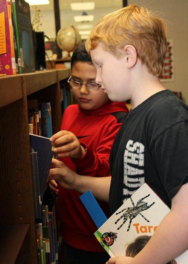 Shadycrest Elementary students Aiden DeLaO (back) and Adrian Morris look through the science shelves in the campus library.