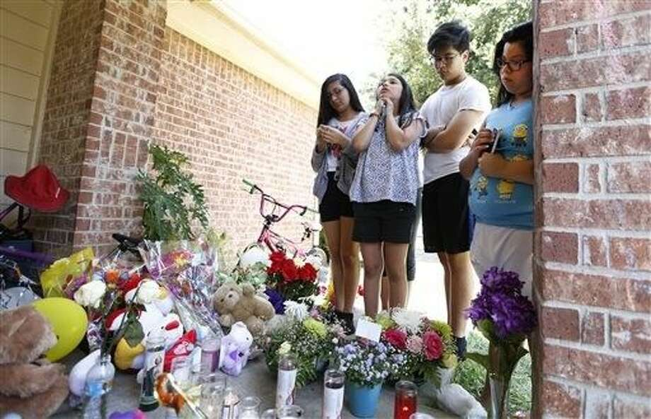 From left, Wendy Antonio, Valerie Perdomo, Carlos Sanchez and Jessica Sanchez brought flowers and offered prayer at a memorial outside of the home of Valerie Jackson, where 6 children and two adults were murdered Saturday night. Photo: Steve Gonzales