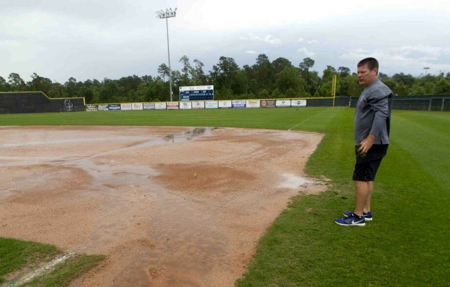 College Park head coach Jason Washburn surveys the baseball field as rain continues to come down at College Park High School Wednesday.