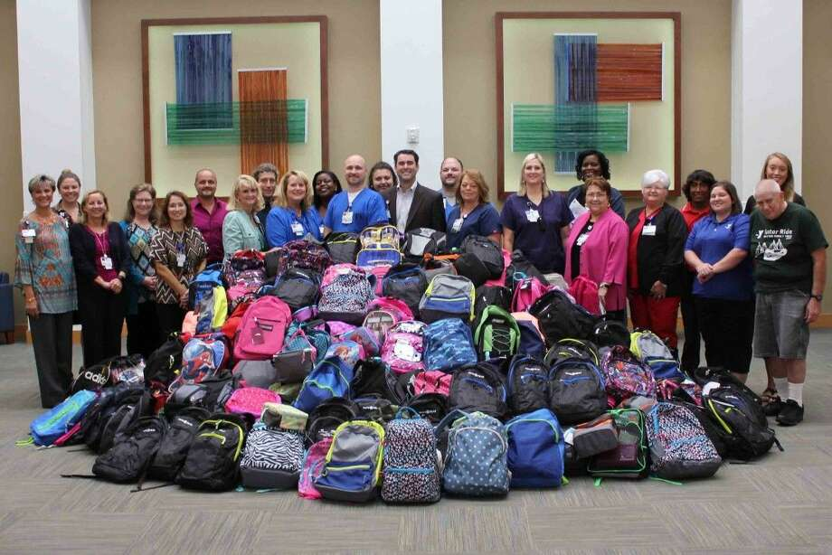The Baytown Family YMCA accepts more than 256 backpacks stuffed with school supplies donated by employees at Houston Methodist San Jacinto Hospital.