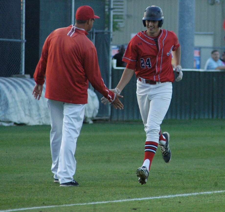 Atascocita senior Matt Willrodt celebrates with coach Eric Matthews as he rounds third after hitting a home run in a 5-4 victory against Kingwood on Friday, April 22, 2016.