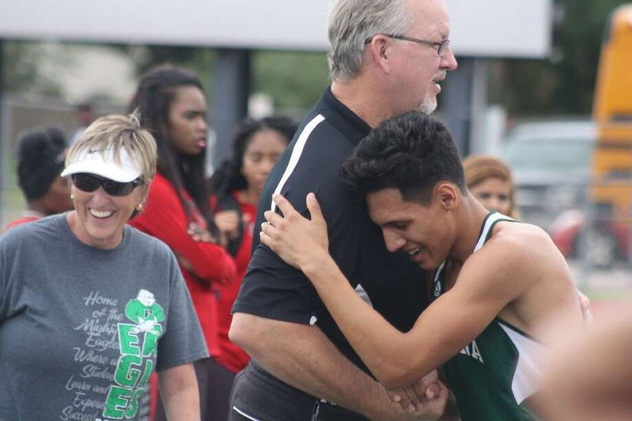 Pasadena High School distance runner Enoch Ramirez leans on campus athletic director Jeff Ganske after Ramirez qualified for the Region III meet in the grueling 3200 Thursday afternoon at Pearland Stadium. That night, Ramirez made it a two-pack trip to regionals with a silver medal in the 1600. Photo: Robert Avery