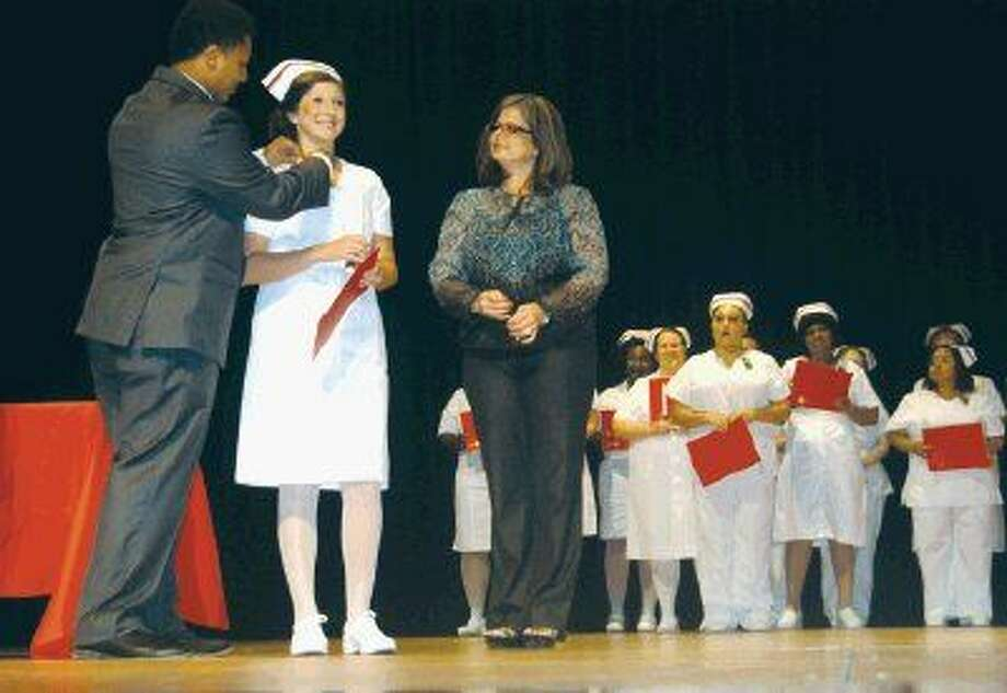 Lee College Vocational Nursing graduate Brittaney Sandefur (center) receives her American Red Cross pin from Donald Sanford (left) as Tracy Allen, director of nursing (right), prepares to add the Lee College pin to Sandefur's lapel and her classmates look on. The Class of Summer 2015, honored at an Aug. 5 ceremony at the Performing Arts Center on campus, included 22 new vocational nurses.