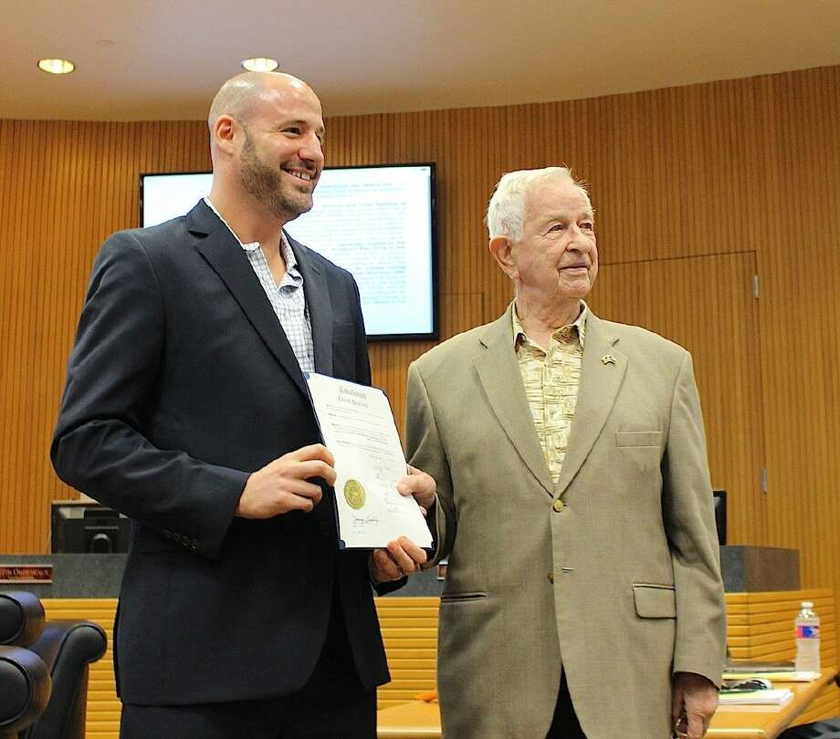 Scott Sherman and Mayor Tom Reid smile as Sherman shows off his Resolution of Appreciation.