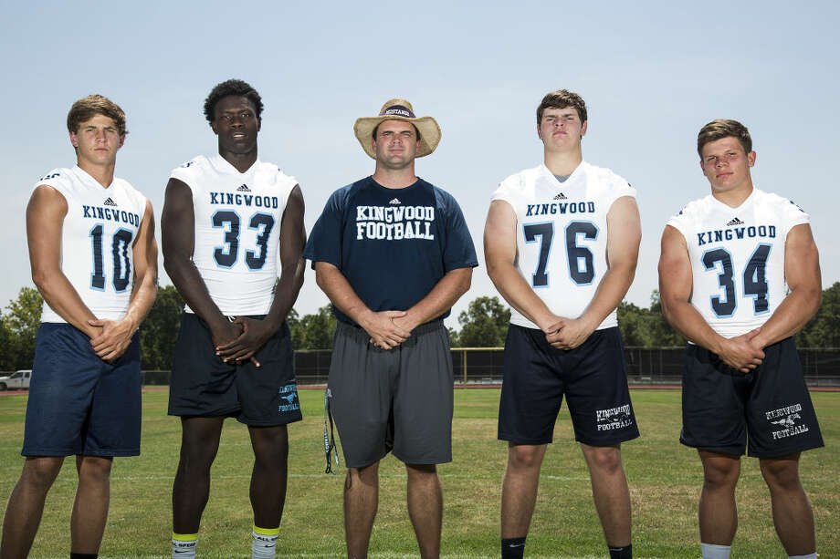 Mustangs quarterback Dawson Trudell (10), running back Sewo Olonilua (33), head coach Berry Campbell, offensive lineman Alec Cruseturner (76) and linebacker Spencer Goodman (34) pose for a portrait Aug. 11, 2015, at Kingwood High School. Photo: ANDREW BUCKLEY