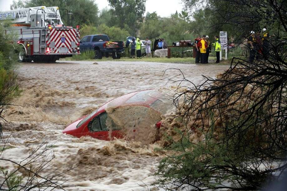 AP photo by Ron MedvescekWater washes over the car after the driver was rescued by members of Northwest Fire District north of Tucson, Ariz., on Monday, Sept. 8, 2014. The Phoenix and Tucson metro areas were hit by heavy rains, causing flooding and damage. More than 3 inches of rain closed parts of several Phoenix freeways. In Tucson, the National Weather Service recorded nearly 2 inches of rain. Photo: Ron Medvescek