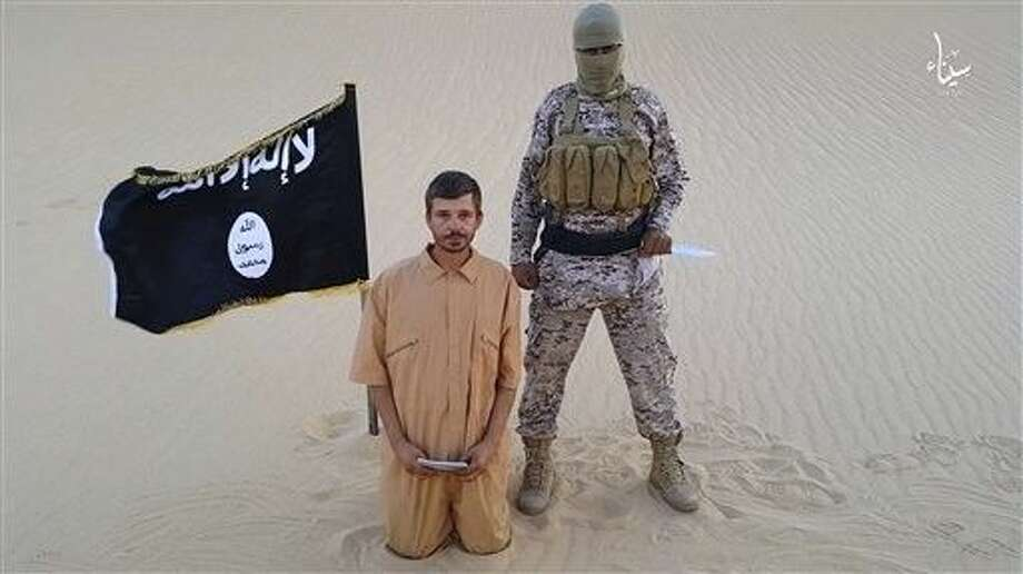 This image made from a militant video posted on a social media site on Wednesday, which has been verified and is consistent with other AP reporting, purports to show a militant standing next to another man who identifies himself as 30-year-old Tomislav Salopek, kneeling down as he reads a message at an unknown location. Photo: Uncredited