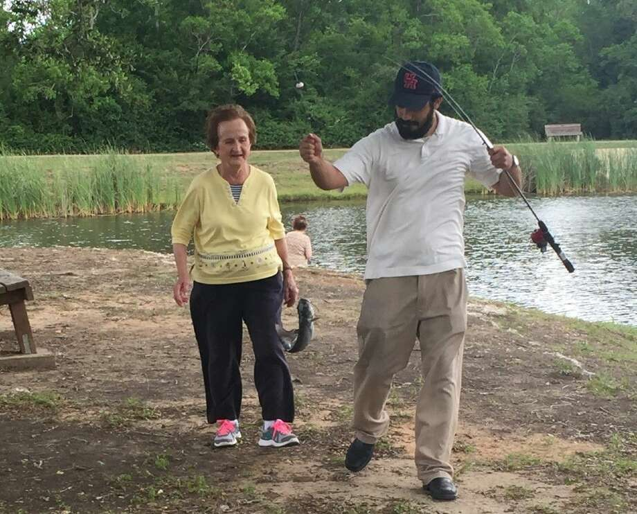 Senior Fish participant Mary Lou Ringler gets some help from a volunteer after reeling one in at last year's event.