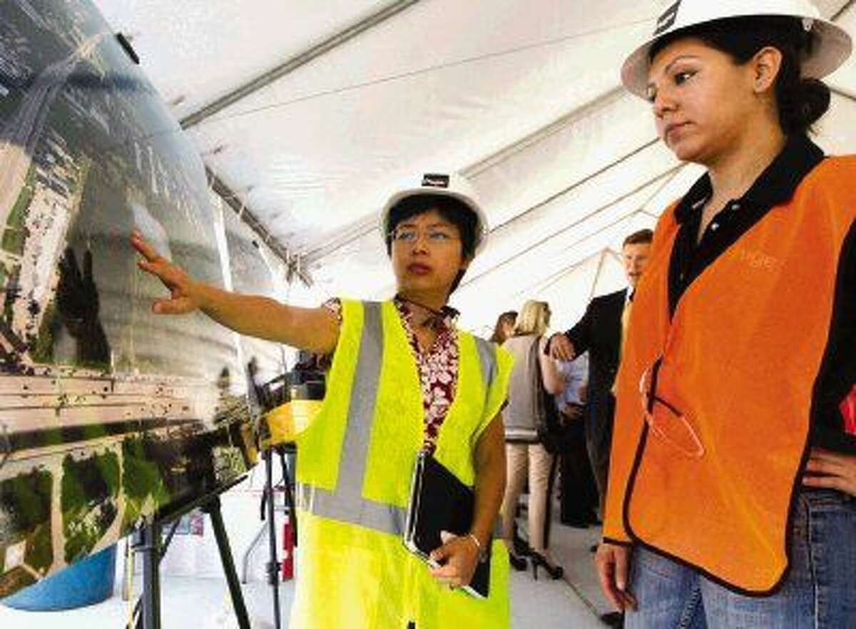 Mie-hwie Kwari, left, and Cristiana Morales look over aerial images of the new Houston Methodist The Woodlands Hospital Thursday. Go to HCNpics.com to view more photos from the event.