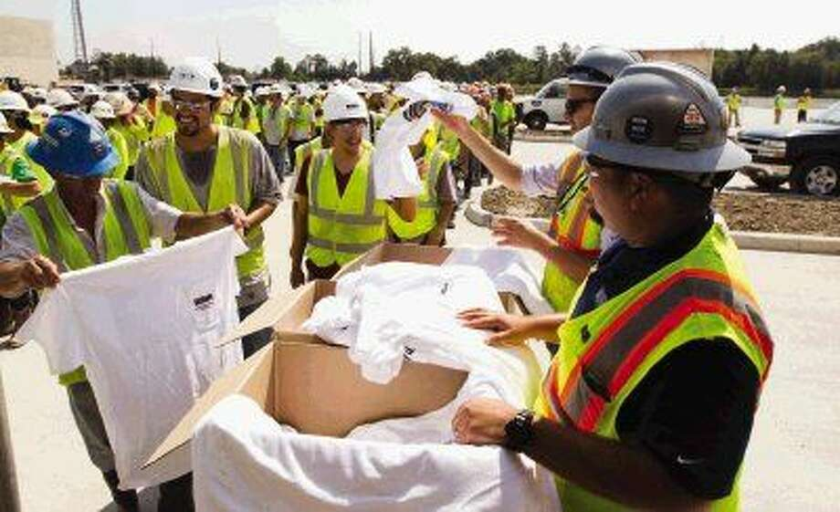 Construction workers pass out T-shirts in celebration of the topping-out celebration for Houston Methodist The Woodlands Hospital Thursday. Go to HCNpics.com to view more photos from the event. Photo: Jason Fochtman