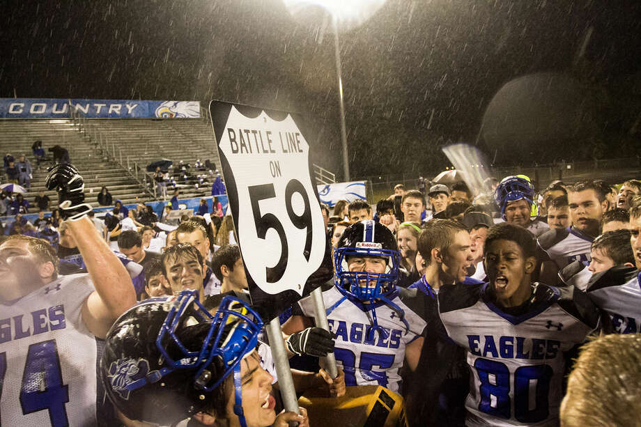 New Caney players celebrated with the Battle Line on 59 trophy in the rain after they defeated Porter 21-7 at Don Ford Stadium last year Photo: Amanda J. Cain