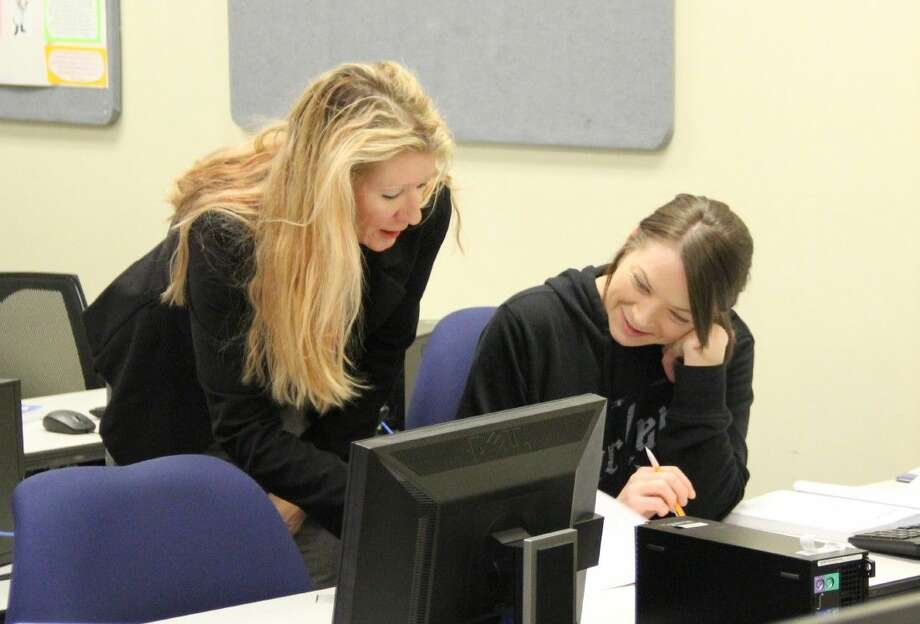 Instructor Kay Frieze assists a student in a health information management class. The College of the Mainland program trains students for a field that is quickly growing, well-paying and flexible.
