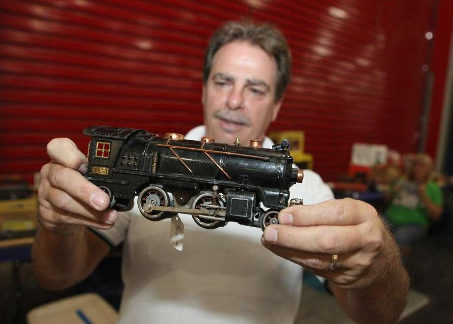 "Pat Ryan of Humble holds a pre-World War II ""O"" gauge Lionel train engine during the set up of the Big Texas Train Show at the George R. Brown Convention Center in Houston, Texas on Friday, Sept. 5, 2014. Photo: Alan Warren"