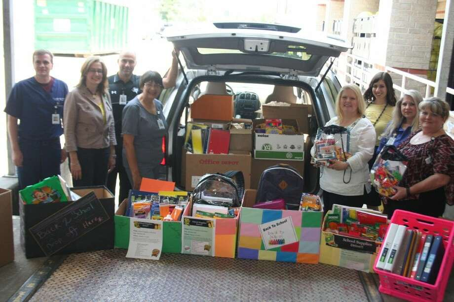 Memorial Hermann Northeast Hospital representatives show off the school supplies collected for students in the Humble Independent School District.
