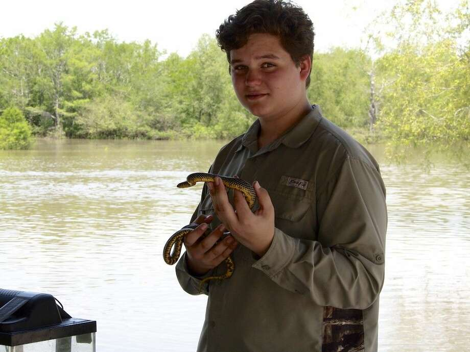 Jake Ballard is a volunteer at the Trinity River National Wildlife Refuge and was on hand Saturday, April 23, to help with the live snake exhibit during the refuge's Earth Day event at Champion Lake. Here Ballard holds a speckled king snake. Photo: Casey Stinnett