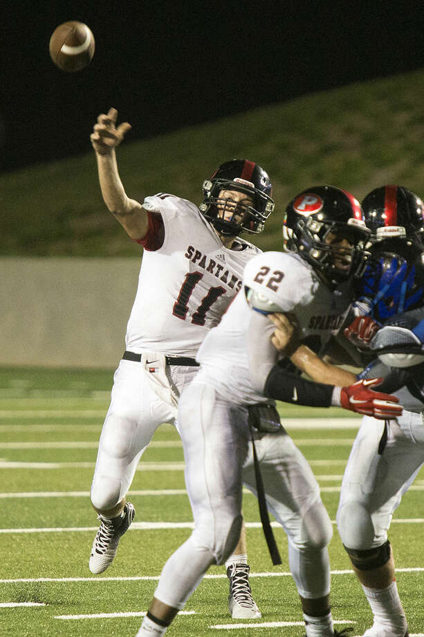 Spartans quarterback Jake Hall passes under pressure during New Caney's 58-33 victory over Porter in the Battle Line on 59 rivalry game Sept. 12, 2014, at Texan Drive Stadium in Porter. Photo: Andrew Buckley