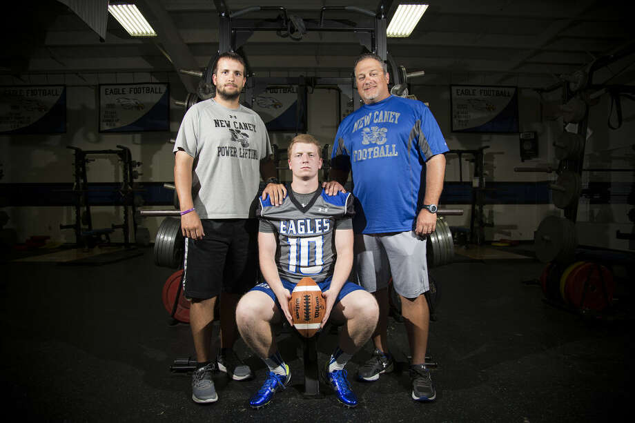 Eagles quarterback Timmy Ware (10) poses for a portrait with quarterbacks coach Billy Noonan, left, and his father, offensive coordinator Blake Ware, Aug. 13, 2015, at New Caney High School. Photo: ANDREW BUCKLEY